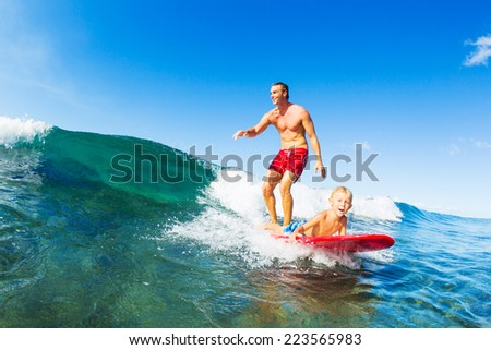 Father and Son Surfing Together Riding Blue Ocean Wave - stock photo