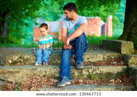 father and son talk, while sitting on old stairs outdoor - stock photo