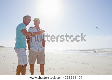 Father and son talking on sunny beach - stock photo