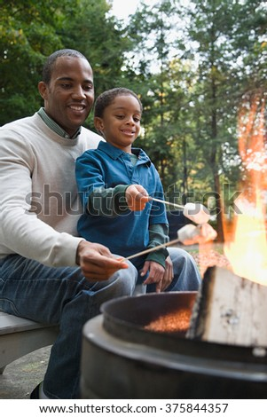 Father and son toasting marshmallows - stock photo