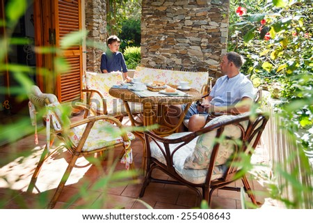 Father and son together on patio on beautiful summer day - stock photo
