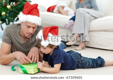 Father and son unwrapping a present lying on the floor - stock photo