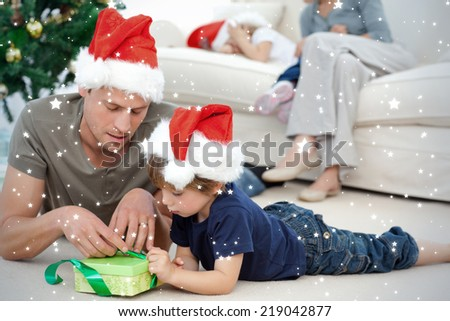 Father and son unwrapping a present lying on the floor against snow - stock photo