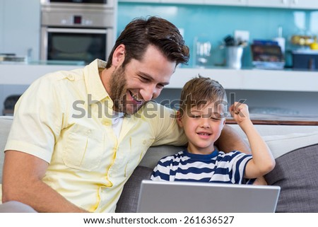 Father and son using laptop on the couch at home in the living room - stock photo