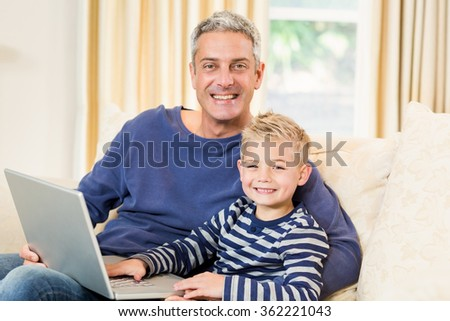 Father and son using laptop on the sofa in living room - stock photo