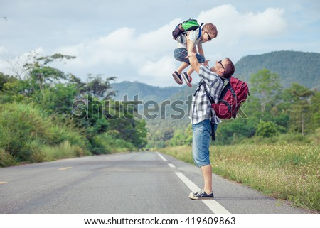 Father and son walking on the road at the day time.  Concept of friendly family. - stock photo