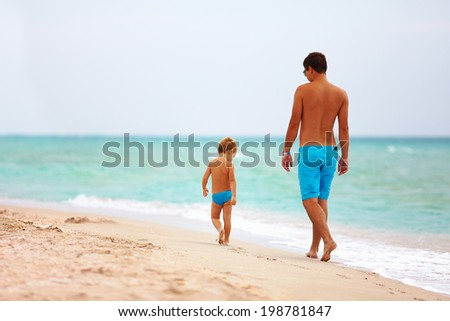 father and son walking the sea beach - stock photo