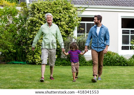 Father and son walking while holding hands with boy at yard - stock photo