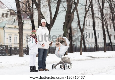 Father and son walking with a baby stroller in a city park on a cold snow day - stock photo