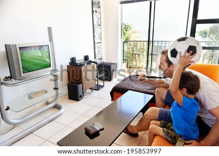 Father and son watching football world cup soccer on tv together in living room on sofa being excited fans - stock photo