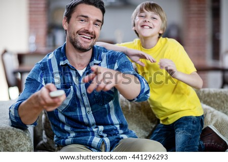 Father and son watching television in living room at home - stock photo