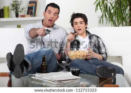 Father and son watching television together - stock photo