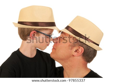 Father and son with hats hugging in studio - stock photo