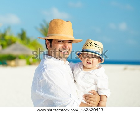 Father and son with panama hats stands on white sandy beach on Maldives - stock photo