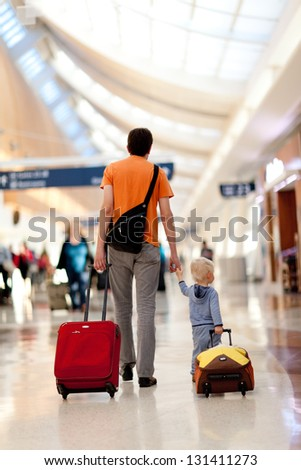 father and son with the luggage at the airport - stock photo