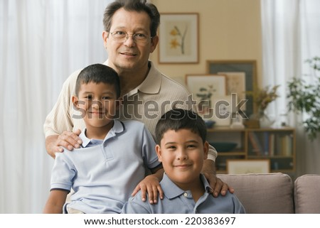 Father and sons smiling for the camera - stock photo