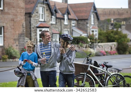Father and Sons stopping in a village in the middle of their bike ride to take a drink. They are wearing casual clothing and smiling. - stock photo
