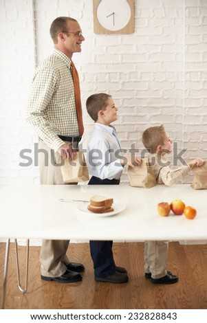 Father and Sons with Sack Lunches - stock photo