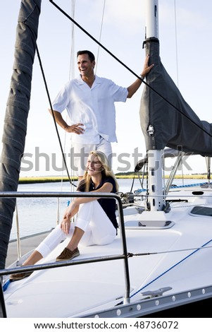 Father and teenage daughter smiling on sailboat at dock on sunny day - stock photo
