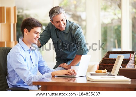 Father And Teenage Son Looking At Laptop Together - stock photo
