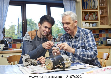 father and teenage son working on car part at kitchen table - stock photo