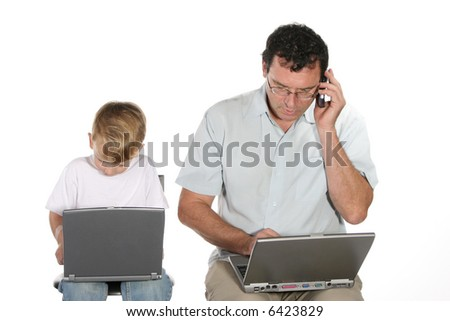 Father and toddler son sitting both working on laptop computers father also using a cell phone - stock photo