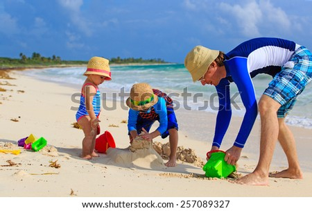 father and two kids playing with sand on summer tropical beach - stock photo