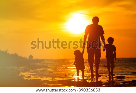 father and two kids walking at sunset - stock photo
