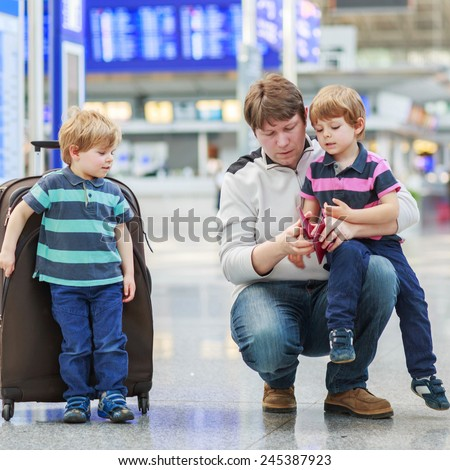 Father and two little kid boys at international airport, traveling together. Dad checking tickets and passes, siblings are waiting for the flight. - stock photo