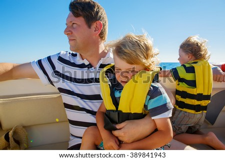 Father and two little kid boys, sons enjoying sailing boat trip. Family vacations on ocean or sea on sunny day. Children smiling. - stock photo