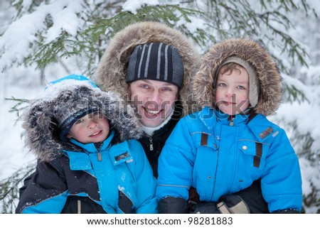 Father and two sons in the winter forest, walk - stock photo