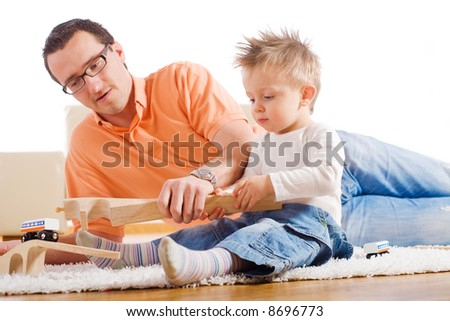 Father and two year old child playing together with wooden toy train. Sitting on floor at home. - stock photo