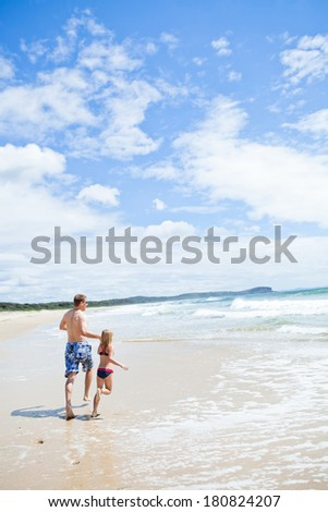 Father and young daughter holding hands and running along beach at edge of water - stock photo