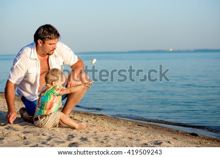 Father and young son are resting on the beach in summer. Dad and son throwing stones in the water on the beach in summer. - stock photo