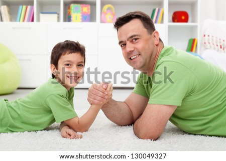 Father arm wrestling with his boy - happy family time together - stock photo