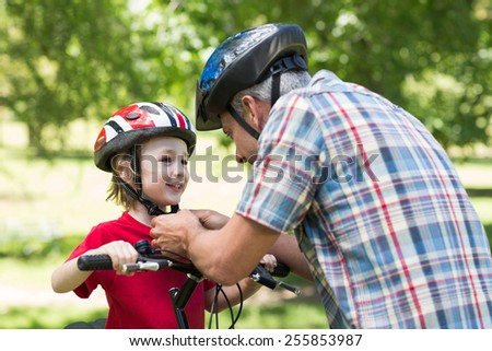 Father attaching his sons cycling helmet on a sunny day - stock photo