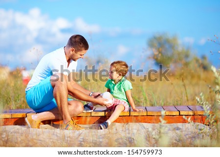 father bandaging injured leg of kid - stock photo