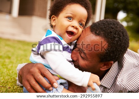 Father bonding with his toddler son in a garden - stock photo