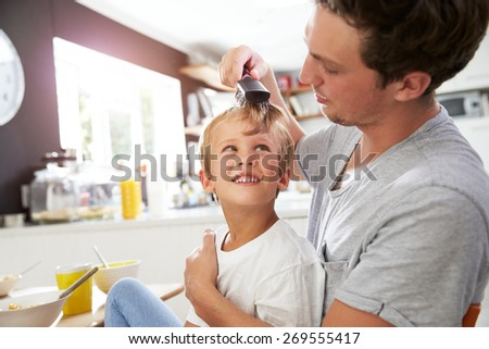 Father Brushing Son's Hair At Breakfast Table - stock photo