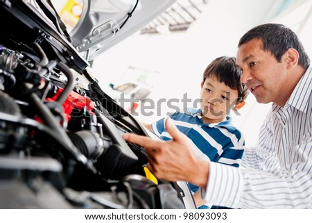 Father buying car with his son and explaining to him about mechanics - stock photo