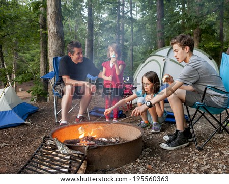 father camping with kids while kids roast marshmallows - stock photo