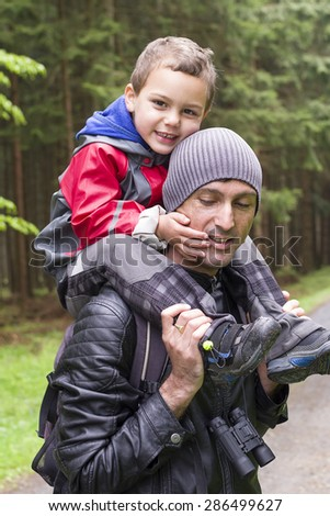 Father carrying child son on shoulders on walk or hide in a forest in nature. - stock photo