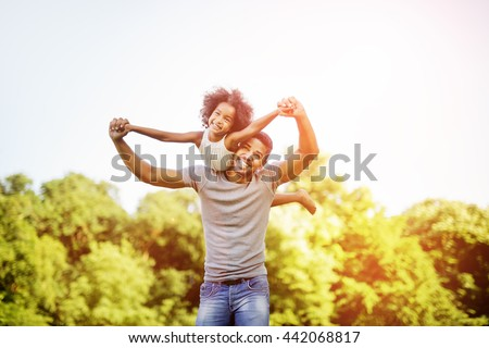 Father carrying daughter piggyback and being truly happy - stock photo