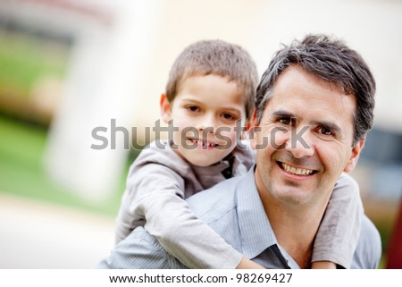 Father carrying his son and smiling - outdoors - stock photo