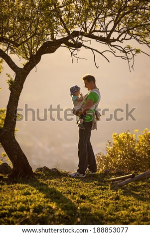 Father carrying his son in sling outdoors  - stock photo