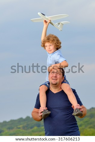 Father carrying son and his plane on shoulders  - stock photo
