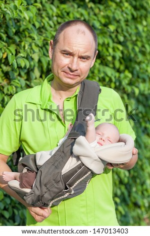 Father carrying son in sling outdoor  - stock photo