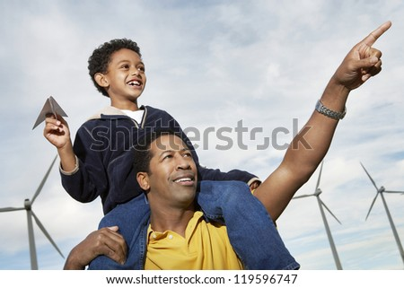 Father carrying son on shoulders while pointing at wind farm - stock photo