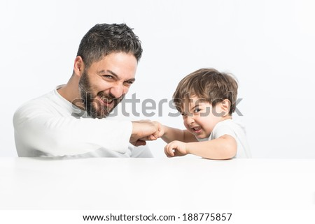 Father challenging his son with funny expressions - stock photo