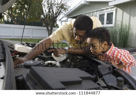 Father checking oil level with his little son - stock photo